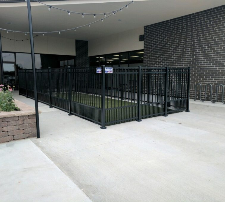A play area for dogs fenced in by black 4 rail ornamental fencing with puppy pickets
