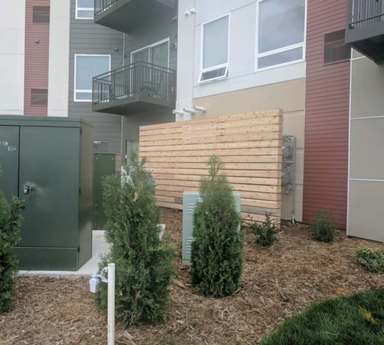 A wood screen in front of a set of utilities on the side of an apartment building