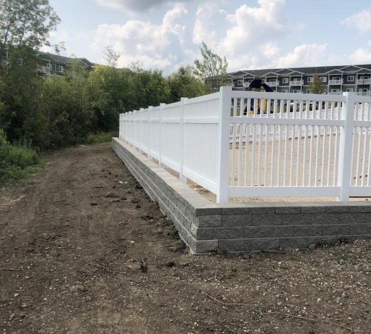 White vinyl picket fence installed around a playground
