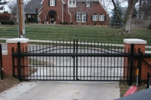 An over arch cantilever gate in front of a residential drive way behind brick pillars