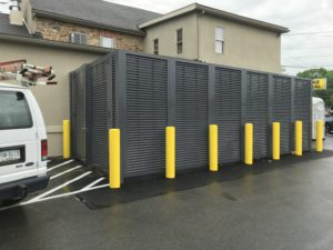 A horizontal louvered mechanical screen system installed at Mission Dispensary with bright yellow traffic columns along its perimeter for extra protection