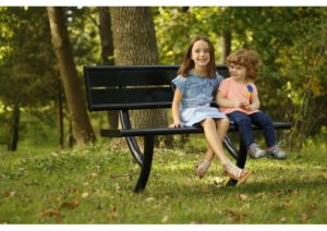 Brother and sister sit side by side on a black park bench
